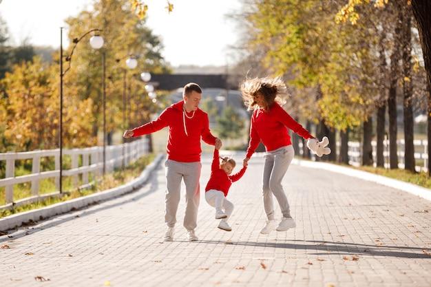 Отец и мать держат маленькую дочь за руки и гуляют в осеннем парке, счастливая семья веселится на открытом воздухе.