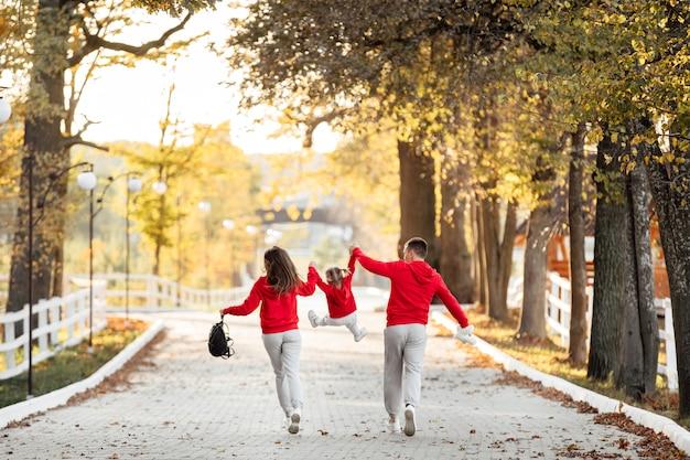 Отец и мать держат маленькую дочку за руки и гуляют в осеннем парке