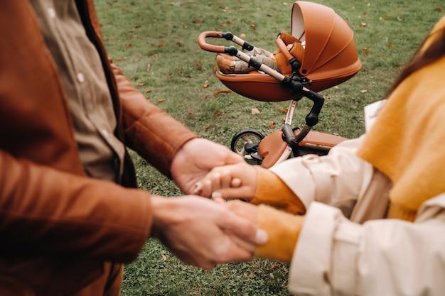 父と母は、秋の公園を散歩している子供と一緒にベビーカーの近くで手をつないでいます。家族が黄金の秋の自然公園を歩きます。