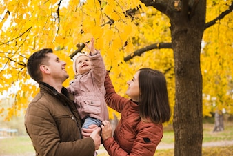 Father and mother holding daughter by tree