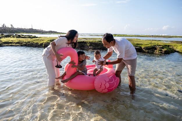 水に浮かぶフラミンゴブイに乗って子供を持つ父親と母親