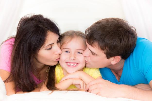 아버지와 어머니가 당신의 아이에게 키스합니다. 집에서 즐거운 시간을 보내는 행복한 가족