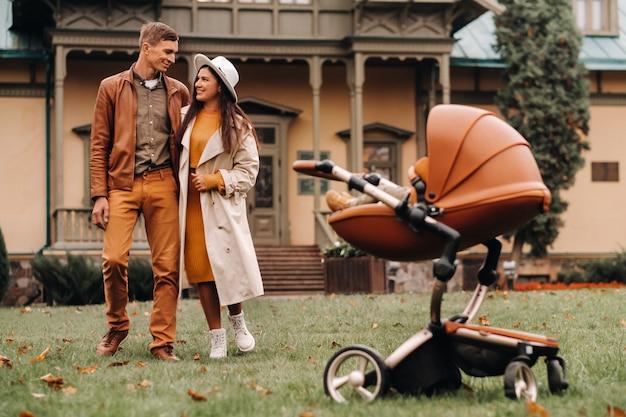 敷地の背景にある秋の公園のベビーカーで子供と散歩中の父と母。家族が黄金の秋の自然公園を歩きます。