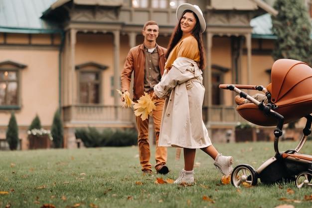 敷地の背景にある秋の公園のベビーカーで子供と散歩中の父と母。家族が黄金の秋の自然公園を歩く