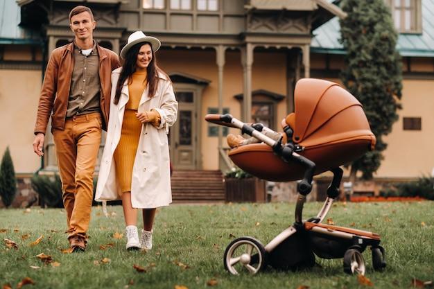 Отец и мать на прогулке с ребенком в коляске в осеннем парке на фоне усадьбы
