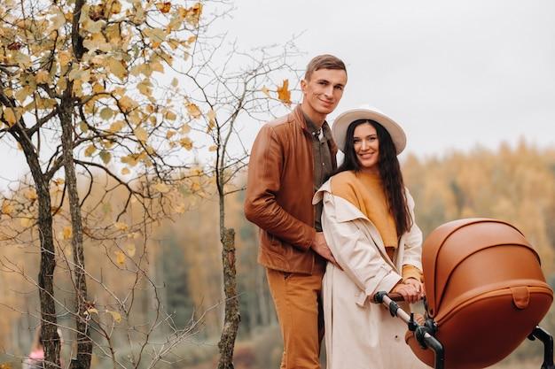 秋の公園でベビーカーと散歩中の父と母。家族は黄金の秋に自然公園を歩きます。