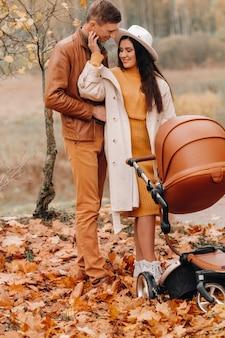 Отец и мать на прогулке с коляской в осеннем парке. семья гуляет по природному парку