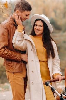 秋の公園でベビーカーと散歩中のお父さんとお母さん。家族は黄金の秋に自然公園を歩きます。