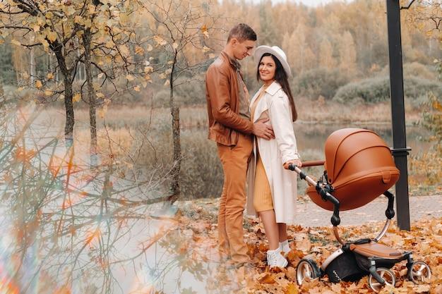 秋の公園でベビーカーと散歩中のお父さんとお母さん