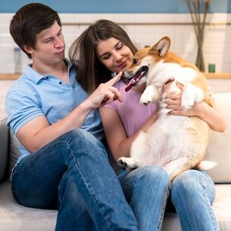 Отец и мать играют с милой собакой