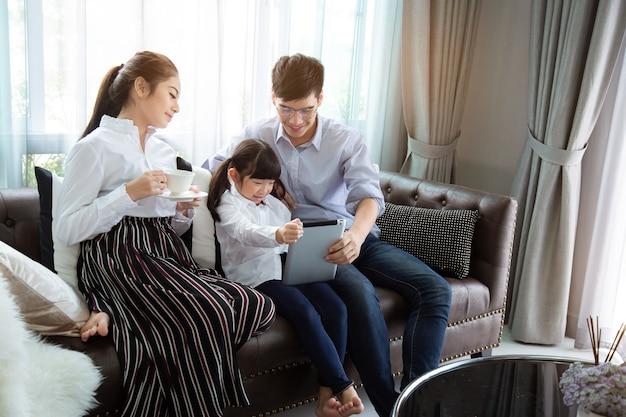 아버지와 어머니는 아이들에게 태블릿을 사용하여 집에서 숙제를 하는 것을 가르치는 아시아 가족은 행복합니다