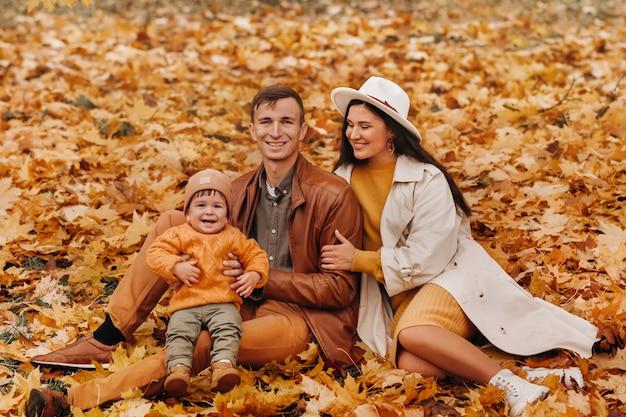 秋の公園に座っている息子と父と母。自然公園の黄金の秋の家族の肖像画。