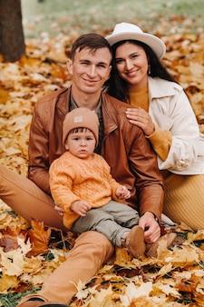 秋の公園に座っている息子と父と母