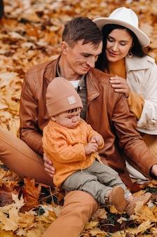 Отец и мать с сыном гуляют в осеннем парке. семья гуляет золотой осенью в природном парке.