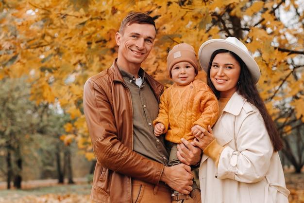 아버지와 아들 이을 공원에서 산책과 어머니. 한 가족이 자연 공원에서 황금빛 가을을 걷고 있습니다.
