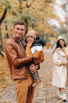 秋の公園を歩いている息子と父と母。家族が自然公園の黄金の秋を歩きます。