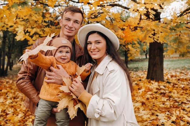 秋の公園を歩く息子と父と母