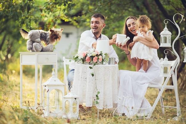 白いテーブルと椅子を持つフィールドの真ん中に自分の娘を持つ父と母