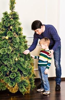 父と息子はクリスマスツリーを飾っています