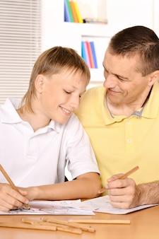 Отец и сын вместе рисуют карандашом за столом