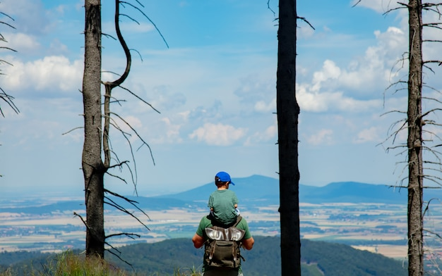 Отец и сын занимаются походами в горы, видом на долину