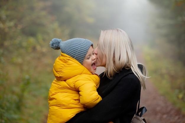 아버지와 아들은 안개 속에서 가을 숲에서 즐거운 시간을 보내고 있습니다.