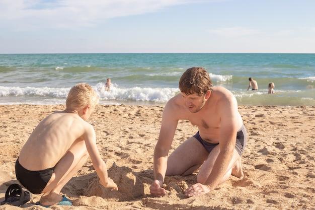 Отец и сын играют на пляже в песчаном морском отдыхе на берегу в солнечный день