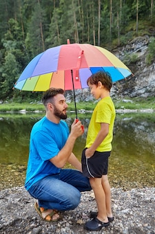 父と息子は川の近くの田舎で父の日を過ごしています、父は雨から彼を保護するために彼の子供の上に傘を持っています。