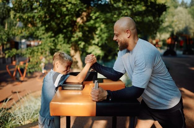 父と息子、腕相撲の練習、屋外の遊び場でのスポーツトレーニング。家族は夏の公園で健康的なライフスタイル、フィットネストレーニングをリードしています