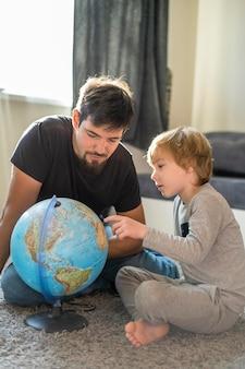 Отец и сын дома с земным шаром