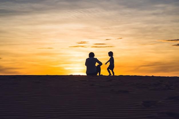 새벽에 붉은 사막에서 아버지와 아들. 어린이 개념으로 여행.