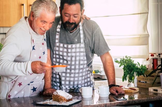 父と息子は楽しんでいる台所で家で一緒に焼く