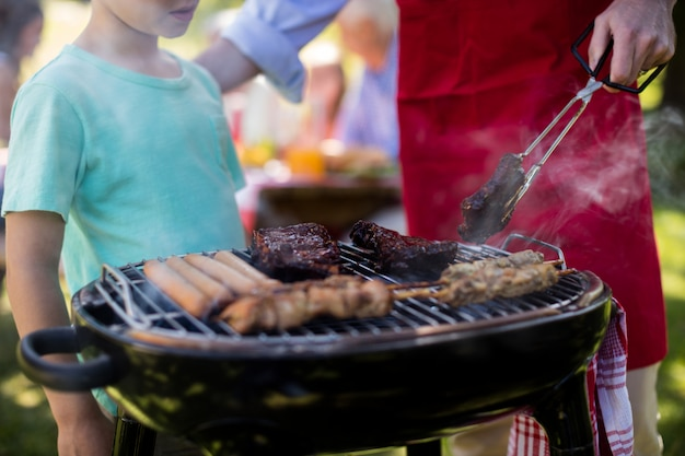 Отец и сын готовят барбекю в парке