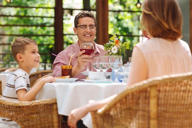 Отец и сын. сияющие счастливые отец и сын смотрят на красивую мать во время вкусного обеда на улице вместе