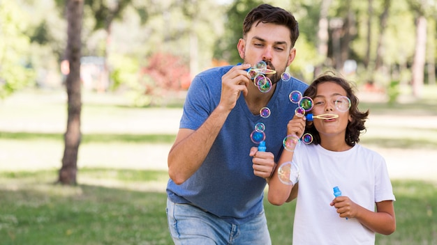 Отец и сын вместе пускают мыльные пузыри в парке