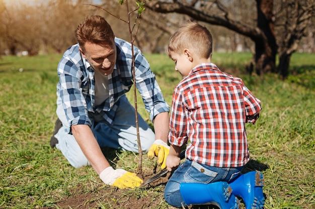 아버지와 아들은 무릎을 꿇고 정원 가꾸기를 즐기고 새로 심은 나무를 돌보고 있습니다.