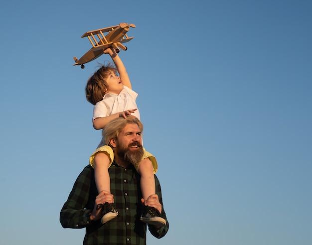 父親の肩に座っているおもちゃの飛行機を持つ父と息子の男の子幸せな父子瞬間父..。