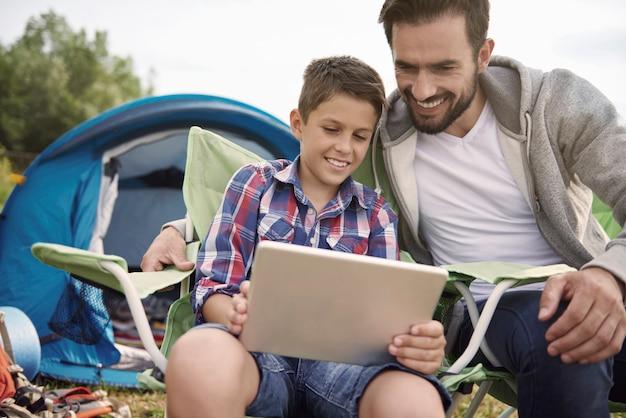 キャンプでインターネットを閲覧している父と息子