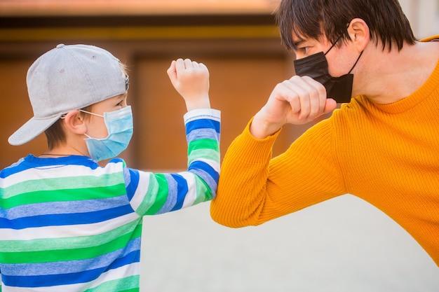 아버지와 아들은 야외에서 팔꿈치를 부딪칩니다. 코로나 바이러스 건강 격리. 사회적 거리두기 개념. 코로나 바이러스 발생. 보호 조치. 아버지는 아들에게 얼굴 보호 마스크를 야외에 두었습니다.