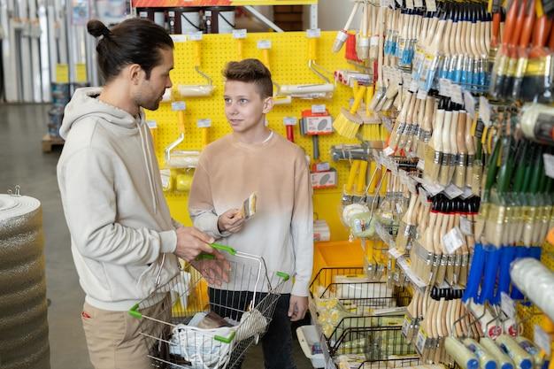 Отец и сын выбирают новую кисть, вместе посещая хозяйственный супермаркет