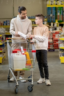 Отец и сын консультируются по поводу товаров для дома во время посещения хозяйственного супермаркета