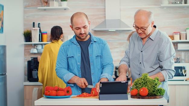 父と息子は、家庭の台所でpcコンピューターのオンラインレシピを使用して夕食のために野菜を調理します。食事の準備中にデジタルタブレットを使用している男性。拡大家族の居心地の良いリラックスした週末。