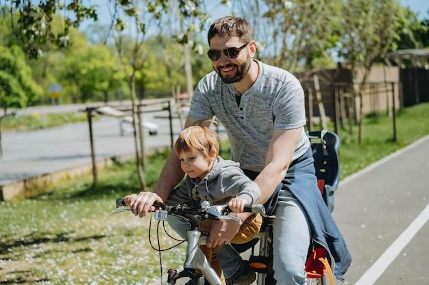 父と息子が自転車レーンに沿って1台の自転車で一緒にサイクリングします。父の日のコンセプト。セレクティブフォーカスの画像。高品質の写真