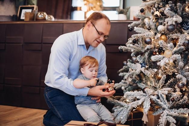 아버지와 아들이 크리스마스 트리를 장식합니다. 아이 방에 있는 크리스마스 트리.