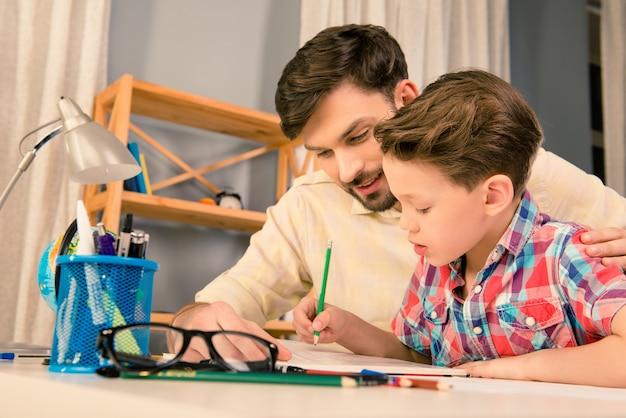 一緒に宿題をしている父と息子