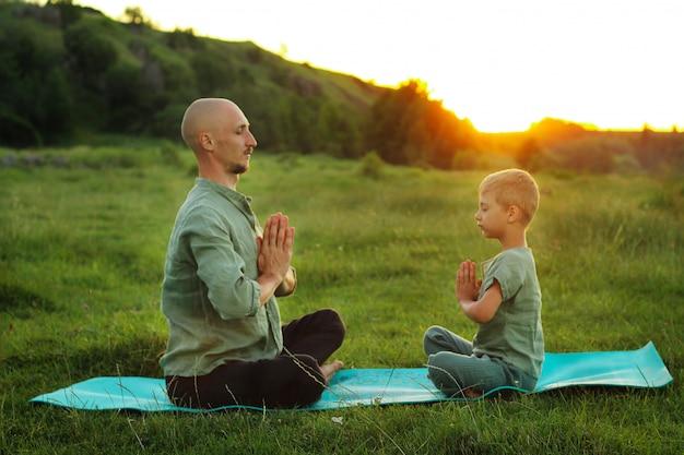 Отец и сын занимаются йогой на открытом воздухе красивый вечерний закат активный образ жизни