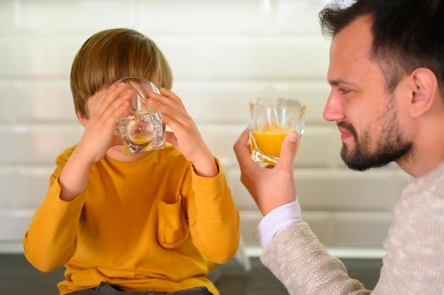 父と息子が台所でオレンジジュースを飲む