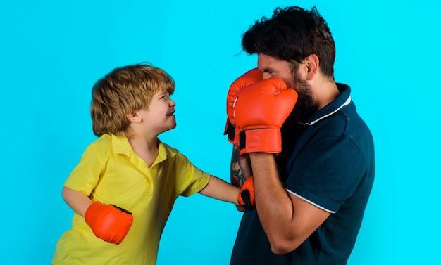 Отец и сын во время тренировки по боксу. папа и ребенок в боксерских перчатках. детская деятельность. тренируемся вместе.