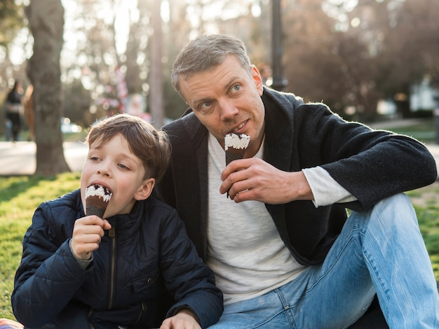 Отец и сын едят мороженое в парке