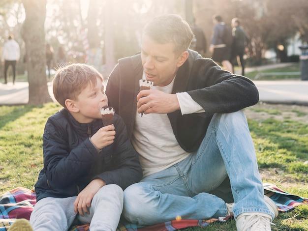 Отец и сын едят мороженое